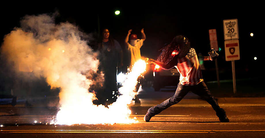 A demonstrator throws back a tear gas container after tactical officers try to break up a group of bystanders Wednesday, Aug. 13, 2014 in West Florissant, Mo. Ferguson has been the site of nightly protests and unrest since 18-year-old Michael Brown was killed during a confrontation with an officer on Saturday. (AP Photo/St. Louis Post-Dispatch, Robert Cohen)
