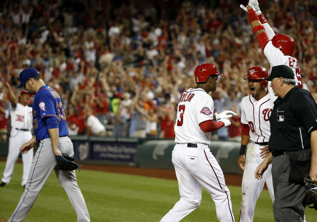 Washington Nationals' Michael Taylor (3) celebrates after four runs scored on his bases-loaded single, with an error by New York Mets center fielder Yoenis Cespedes, as Mets starting pitcher Matt Harvey (33) walks back to the mound during the sixth inning of a baseball game at Nationals Park, Tuesday, Sept. 8, 2015, in Washington. (AP Photo/Alex Brandon)