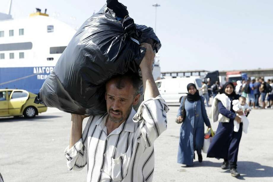 A Syrian man carries a plastic bag with his belongings after his arrival from the southeastern Greek island of Kos to the Athens' port of Piraeus on Tuesday, Sept. 8, 2015. About 600 migrants and refugees arrived with the ferry Diagoras as Frontex, the EU border agency, says more than 340,000 asylum seekers have entered the 28-nation bloc this year, the majority fleeing war and human rights abuses in Syria, Afghanistan, Iraq, Somalia and Eritrea. (AP Photo/Thanassis Stavrakis)