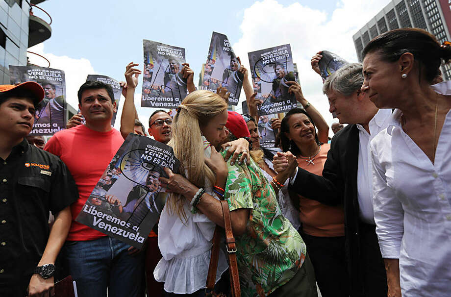 Lilian Tintori, wife of opposition leader Leopoldo Lopez, center left, and a supporter embrace outside of the Justice Palace, as Tintori arrives to attend the second session of Lopez's trial, in Caracas, Venezuela, Wednesday, Aug. 13, 2014. Lopez, who is the head of the Popular Will Party, is charged with inciting violence at early demonstrations. Before turning himself in to authorities in February, he had been spearheading a movement to force President Nicolas Maduro's resignation. Pictured at right is Lopez's mother Antonieta Mendoza de Lopez. (AP Photo/Ariana Cubillos)