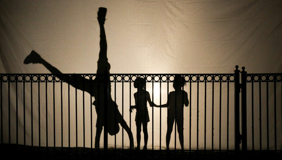 Hour photo/Chris Palermo. Children's silhouettes are projects on a screen as they dance around at the BridgemanPacker dance troupe performance at Roodner Court Wednesday night.