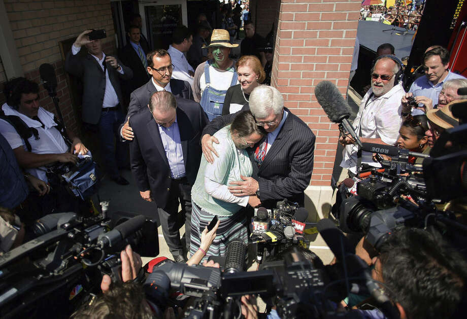 Rowan County clerk Kim Davis, center, hugs her attorney, Matt Staver, with Republican presidential candidate Mike Huckabee, center left, next to her after being released from the Carter County Detention Center, Tuesday, Sept. 8, 2015, in Grayson, Ky. Davis, the Kentucky county clerk who was jailed for refusing to issue marriage licenses to gay couples, was released Tuesday after five days behind bars. (Jonathan Palmer/The Courier-Journal via AP) NO SALES; MAGS OUT; NO ARCHIVE; MANDATORY CREDIT