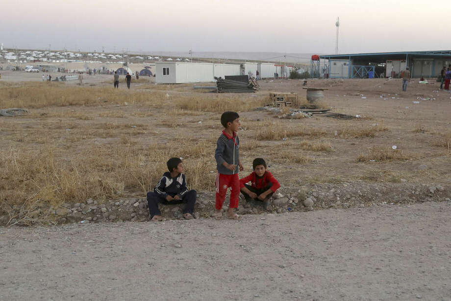 Displaced Iraqi boys from the Yazidi community wait at the entrance of the camp of Bajid Kandala as they look for their family members who they became separated from during their escape, at Feeshkhabour town near the Syria-Iraq border, in Iraq Saturday, Aug. 9, 2014. The displacement of at least tens of thousands of Yazidis- Kurdish speakers of an ancient Mesopotamian faith - means yet another Iraqi minority have been peeled away as extremists continue their sweep of Iraq, seizing territory they brutally administer. The Islamic State group fighters already caused the expulsion of Iraq's Christians, Shiite Muslims and adherents of the tiny Shabak faith. The hardliners see other religious groups as heretics who may be killed or forced to submit to their rule. (AP Photo/ Khalid Mohammed)