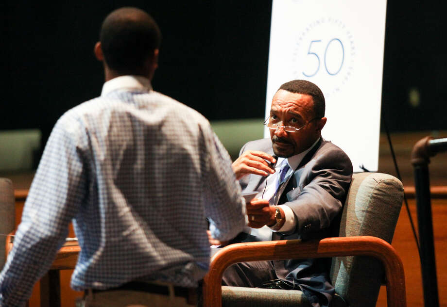 """Hour photo/Chris Palermo. Kweisi Mfume gives Michael Newtown a copy of """"The NAACP Real World Guide to Interacting with Law Enforcement"""" after he asked about his opinion of poice brutality. Mfume spoke with students before his community lecture and conversation on """"The Relevance of Community Colleges Today"""" at Norwalk Community College Wednesday evening."""