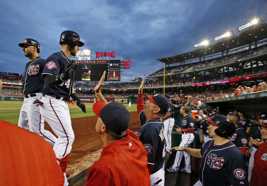 Washington Nationals' Bryce Harper, second from left, is congratulated for his solo home run during the first inning of a baseball game against the New York Mets at Nationals Park, Wednesday, Sept. 9, 2015, in Washington. (AP Photo/Alex Brandon)