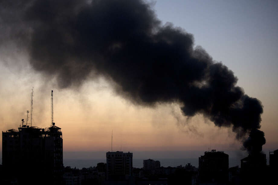 Smoke raises over Gaza City after an Israeli airstrike Sunday, Aug. 10, 2014. (AP Photo/Dusan Vranic)
