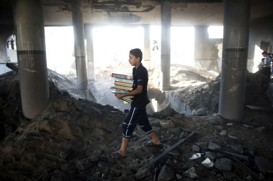 A Palestinian boy carries religion books he salvaged from the Martyr Imam Hassan al-banna mosque in Zeitoun neighborhood in Gaza City, after it was hit by an Israeli airstrike, Saturday, Aug. 9, 2014. (AP Photo/Dusan Vranic)