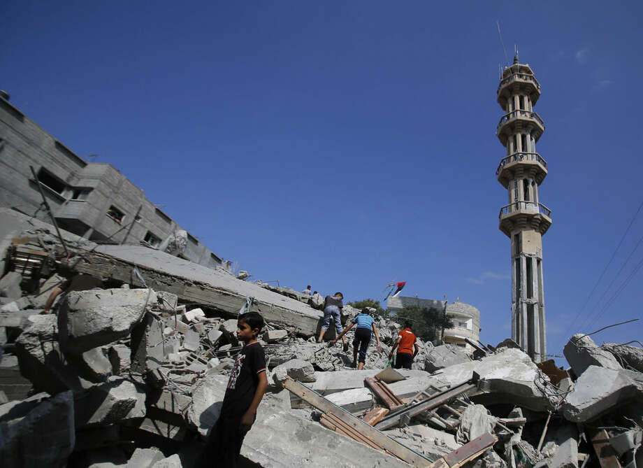 Palestinians stand in rubble of the al-Qassam mosque in Nuseirat refugee camp, central Gaza Strip, after it was hit by an Israeli airstrike, Saturday, Aug. 9, 2014. (AP Photo/Hatem Moussa)