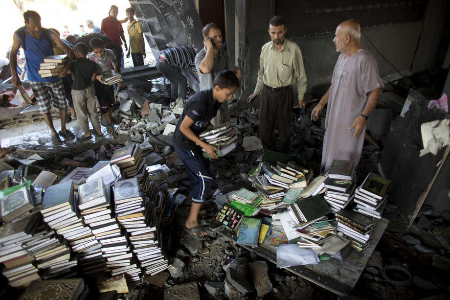 Palestinians try to salvage religion books from the Martyr Imam Hassan al-banna mosque in Zeitoun neighborhood in Gaza City, after it was hit by an Israeli airstrike, Saturday, Aug. 9, 2014. (AP Photo/Dusan Vranic)