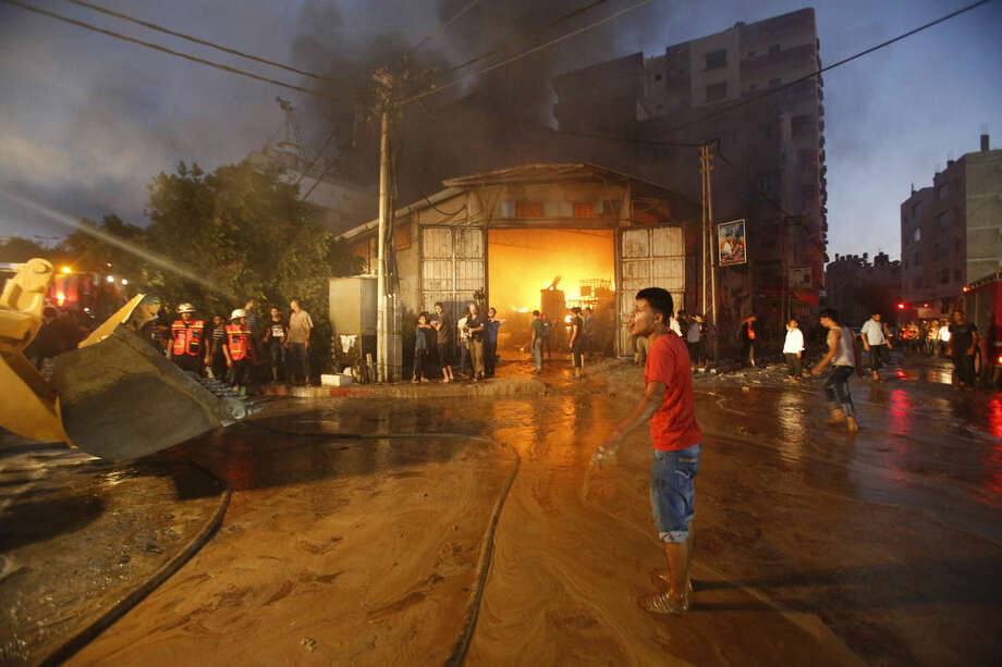 Firefighters try to extinguish fire after a cleaning materials factory was hit by an Israeli airstrike in Gaza City on Sunday, Aug. 10, 2014. (AP Photo/Hatem Moussa)