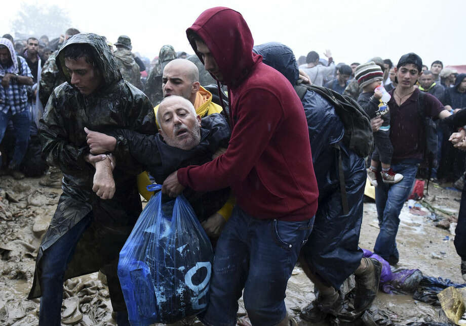Migrants help an elderly man to pass from the northern Greek village of Idomeni to southern Macedonia, Thursday, Sept. 10, 2015. Thousands of people, including many families with young children, braved torrential downpours to cross Greeceís northern border with Macedonia early Thursday, after Greek authorities managed to register about 17,000 people on the island of Lesbos in the space of a few days, allowing them to continue their journey north into Europe. (AP Photo/Giannis Papanikos)