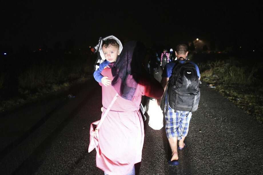 A woman holds a child as other refugees and migrants walk to the border checkpoint at the northern Greek village of Idomeni, Thursday, Sept. 10, 2015. Thousands of people, including many families with young children, braved torrential downpours to cross Greece's northern border with Macedonia early Thursday, after Greek authorities managed to register about 17,000 people on the island of Lesbos in the space of a few days, allowing them to continue their journey north into Europe. (AP Photo/Giannis Papanikos)