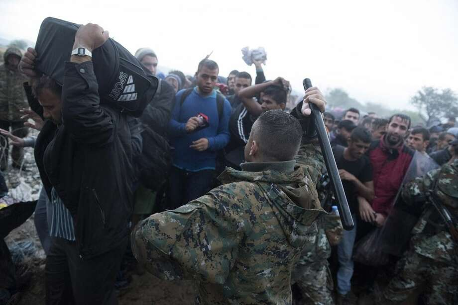 A Macedonian border policeman scuffles with refugees and migrants as they wait to pass in heavy rainfall from the northern Greek village of Idomeni to southern Macedonia, Thursday, Sept. 10, 2015. Thousands of people, including many families with young children, braved torrential downpours to cross Greece's northern border with Macedonia early Thursday, after Greek authorities managed to register about 17,000 people on the island of Lesbos in the space of a few days, allowing them to continue their journey north into Europe. (AP Photo/Giannis Papanikos)