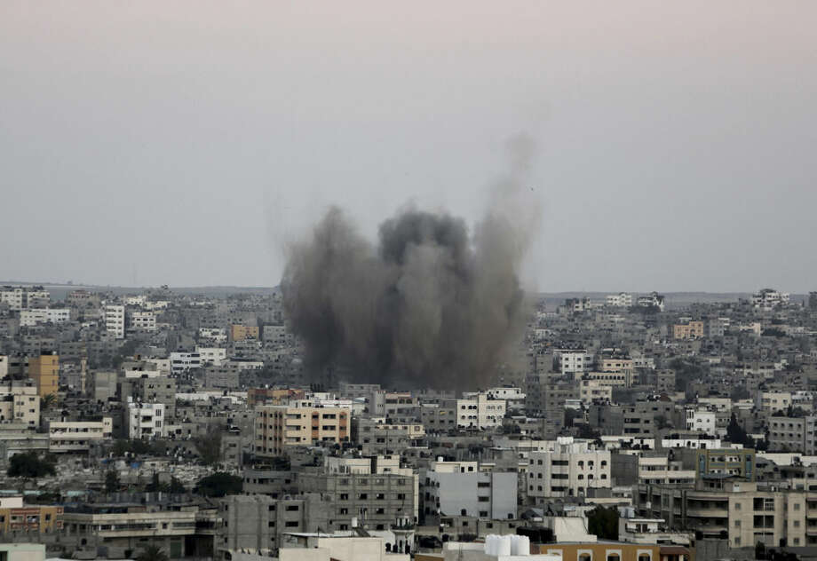 Smoke and dust rise after an Israeli strike in Gaza City in the northern Gaza Strip on Sunday, Aug. 10, 2014. (AP Photo/Adel Hana)