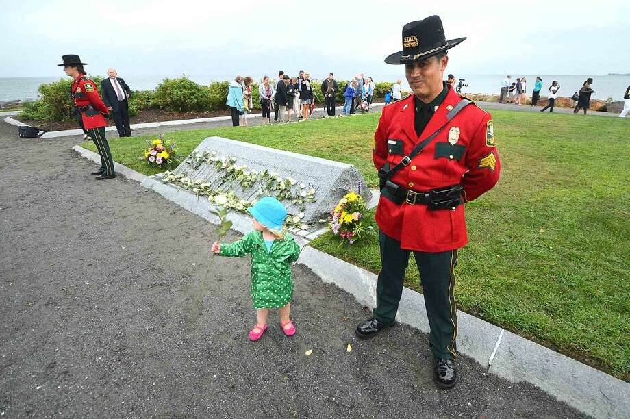 Hour Photo/Alex von Kleydorff During the Connecticut Remembers September 11th Memorial Ceremony 2 yr old Cece Butzbaugh looks for just the right spot to place the white rose she has for her uncle John Henwood