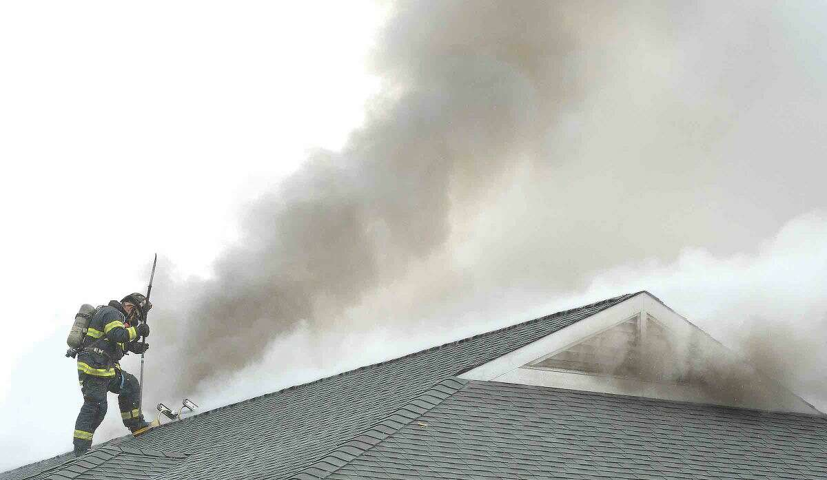 Hour Photo/Alex von Kleydorff Norwalk Firefighters vent the roof of a structure on fire at Shorehaven Golf Club on Thursday