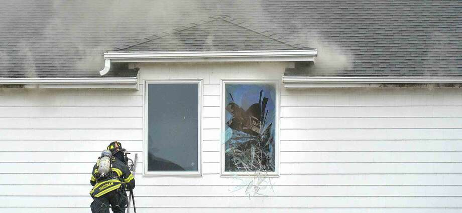 Hour Photo/Alex von Kleydorff A window is broken to vent from the inside at Firefighters respond to a structure fire at Shorehaven Golf Club on Thursday