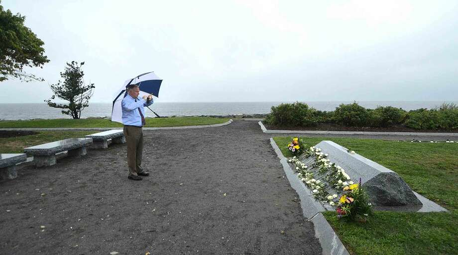 Hour Photo/Alex von Kleydorff During the Connecticut Remembers September 11th Memorial Ceremony, Steve Woods takes a photo of the placed roses on the marker as the rain starts to fall at Sherwood island