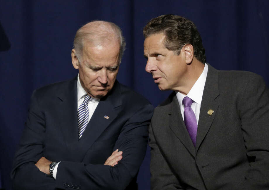 Vice President Joe Biden and New York Gov. Andrew Cuomo talk prior to speaking at a labor rally, Thursday, Sept. 10, 2015, in New York. Cuomo is proposing to raise the state minimum wage to $15 an hour. (AP Photo/Mark Lennihan)
