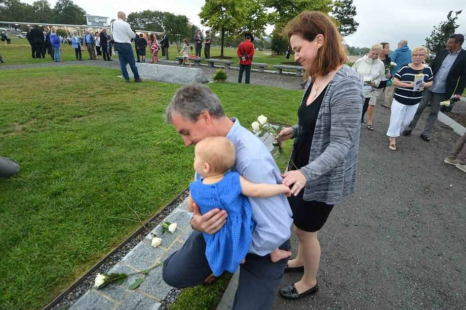 Hour Photo/Alex von Kleydorff During the Connecticut Remembers September 11th Memorial Ceremony Joel and Victoria Statkevicus along with 1yr old daughter Anastasia place a white rose on the name of his brother Derek