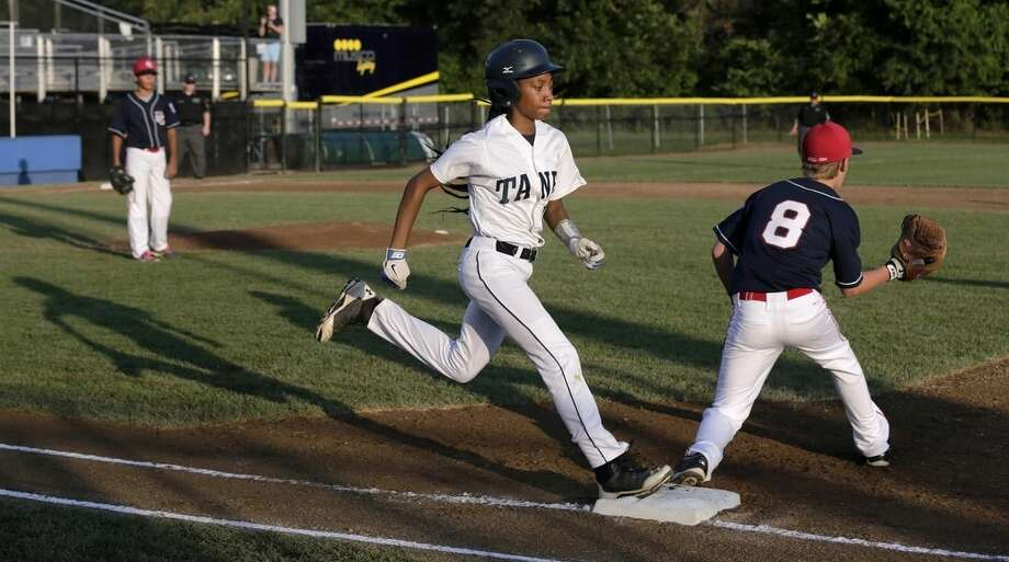 In this Aug. 6, 2014, photo, Pennsylvania's Mo'Ne Davis steps on first as she beats the throw on a single against the District of Columbia during a baseball game in the Little League Eastern Regionals at Breen Stadium in Bristol, Conn. Davis and New Jersey's Kayla Roncin are competing to make it to the Little League World Series, a rare feat for girls. (AP Photo/Charles Krupa)