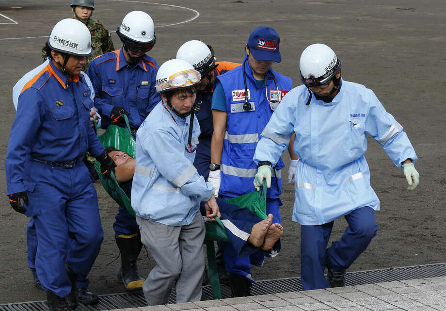 A man is carried by firefighters after being rescued by a helicopter, in Joso, Ibaraki prefecture, northeast of Tokyo, Friday, Sept. 11, 2015. Search and rescue of residents stranded and missing resumed Friday, a day after raging floodwaters broke through an embankment and swamped the city, washing away houses and forcing dozens of people to rooftops. (AP Photo/Shizuo Kambayashi)