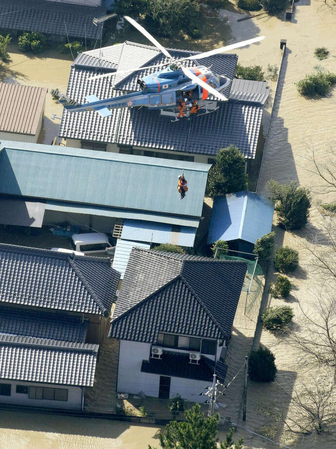 A stranded resident is airlifted by a helicopter during a rescue operation in Joso, Ibaraki prefecture, northeast of Tokyo, Friday, Sept. 11, 2015. Rescue workers searched through the flooded city on Friday, hunting for missing people a day after raging floodwaters broke through an embankment and washed away houses and forced dozens of people to rooftops. In Joso city, dozens of residents were airlifted by military helicopters after waiting overnight. (Masanori Takei/Kyodo News via AP) JAPAN OUT, CREDIT MANDATORY