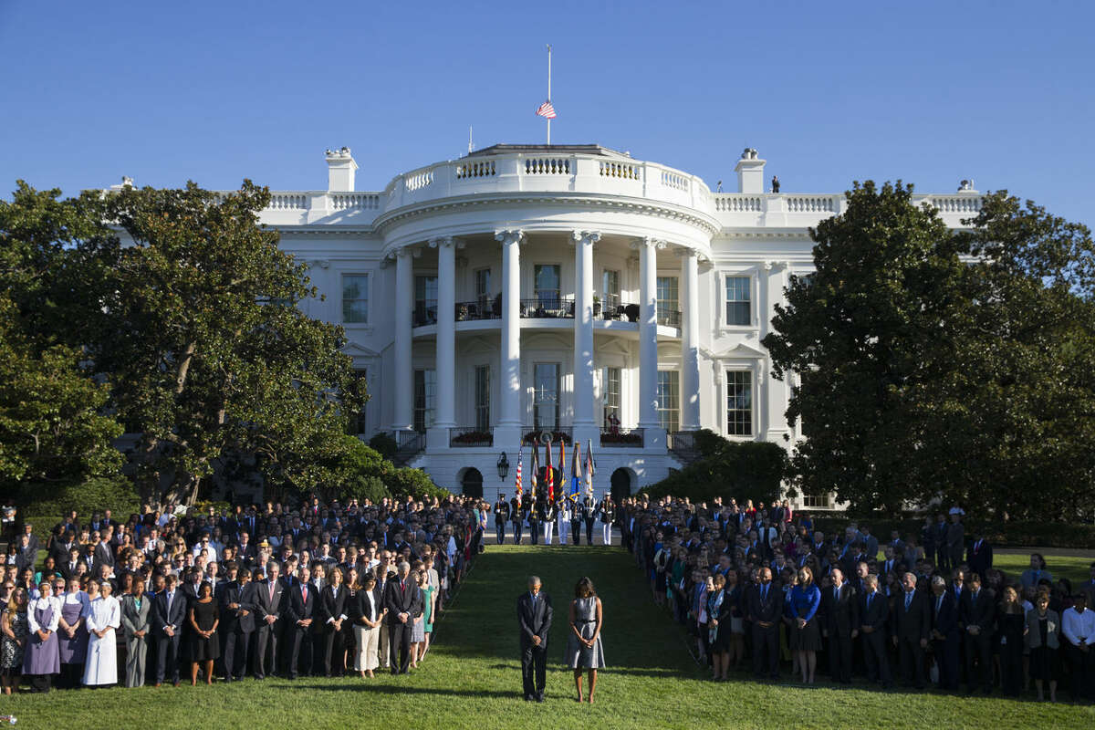 President Barack Obama, first lady Michelle Obama, and others. pause on the South Lawn of the White House in Washington, Friday, Sept. 11, 2015, as they observe a moment of silence to mark the 14th anniversary of the 9/11 attacks. (AP Photo/Evan Vucci)