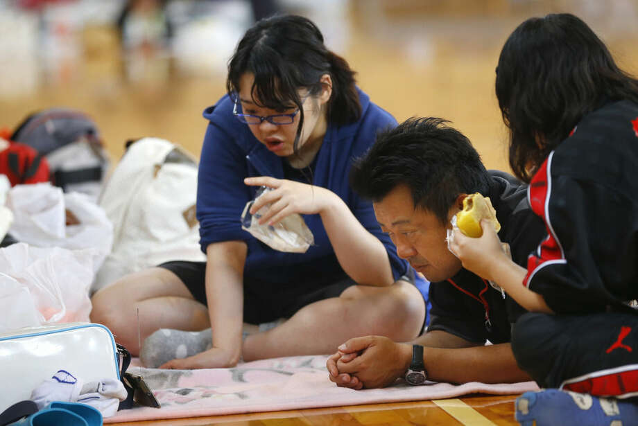 A family watches TV news at an evacuation center after taking shelter in Joso, Ibaraki prefecture, northeast of Tokyo, Friday, Sept. 11, 2015. Search and rescue of residents stranded and missing resumed Friday, a day after raging floodwaters broke through an embankment and swamped the city, washing away houses and forcing dozens of people to rooftops. More than 30,000 were ordered to flee their homes. (AP Photo/Shizuo Kambayashi)