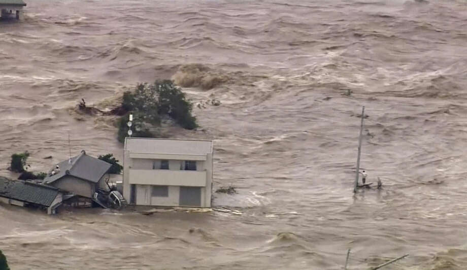 In this photo made off video provided by Japan's Tokyo Broadcasting System (TBS) television network, a man, right, stands stranded in the middle of raging floodwaters before being rescued by a military helicopter in Joso, Ibaraki prefecture, Thursday, Sept. 10, 2015. Raging floodwaters broke through a berm Thursday and swamped the city near Tokyo, washing away houses, forcing dozens of people to rooftops to await helicopter rescues and leaving one man clinging for his life to a utility pole. (TBS TV via AP) JAPAN OUT, NO SALES, TV OUT, MANDATORY CREDIT: TBS TV