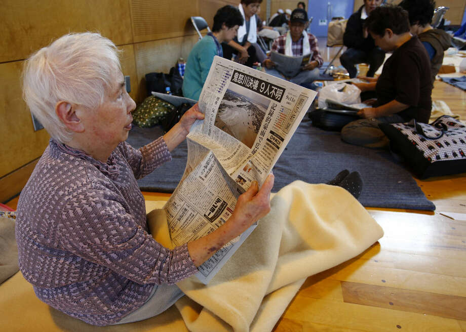 An evacuee reads a newspaper reporting flooding at an evacuation center in Joso, Ibaraki prefecture, northeast of Tokyo, Friday, Sept. 11, 2015. Search and rescue of residents stranded and missing resumed Friday, a day after raging floodwaters broke through an embankment and swamped the city, washing away houses and forcing dozens of people to rooftops. More than 30,000 were ordered to flee their homes. (AP Photo/Shizuo Kambayashi)