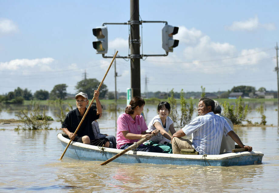 Residents paddle a boat past a traffic light in the flooded road in Joso, Ibaraki prefecture, northeast of Tokyo, Friday, Sept. 11, 2015. The sun came out a day after a raging river washed away houses and forced people to rooftops as dozens of residents were airlifted out by military helicopters Friday morning after waiting overnight in the city. (Kyodo News via AP) JAPAN OUT, CREDIT MANDATORY