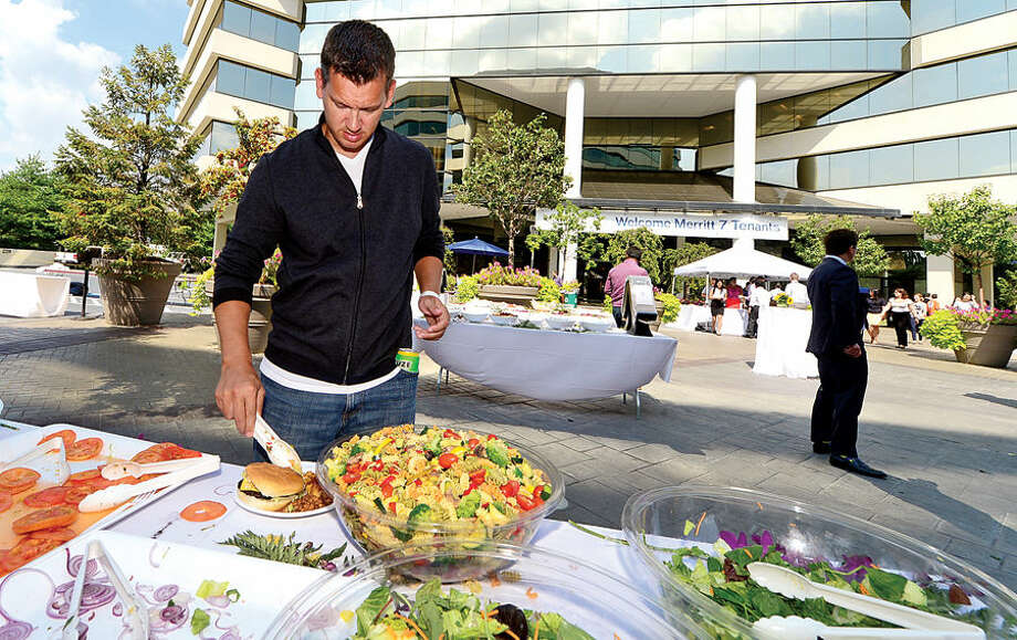 Hour photo / Erik Trautmann Datto employee Nick Hagen grabs a bit of salad during the Merritt 7 Tenant Appreciation picnic Wednesday at 601 Merritt 7.