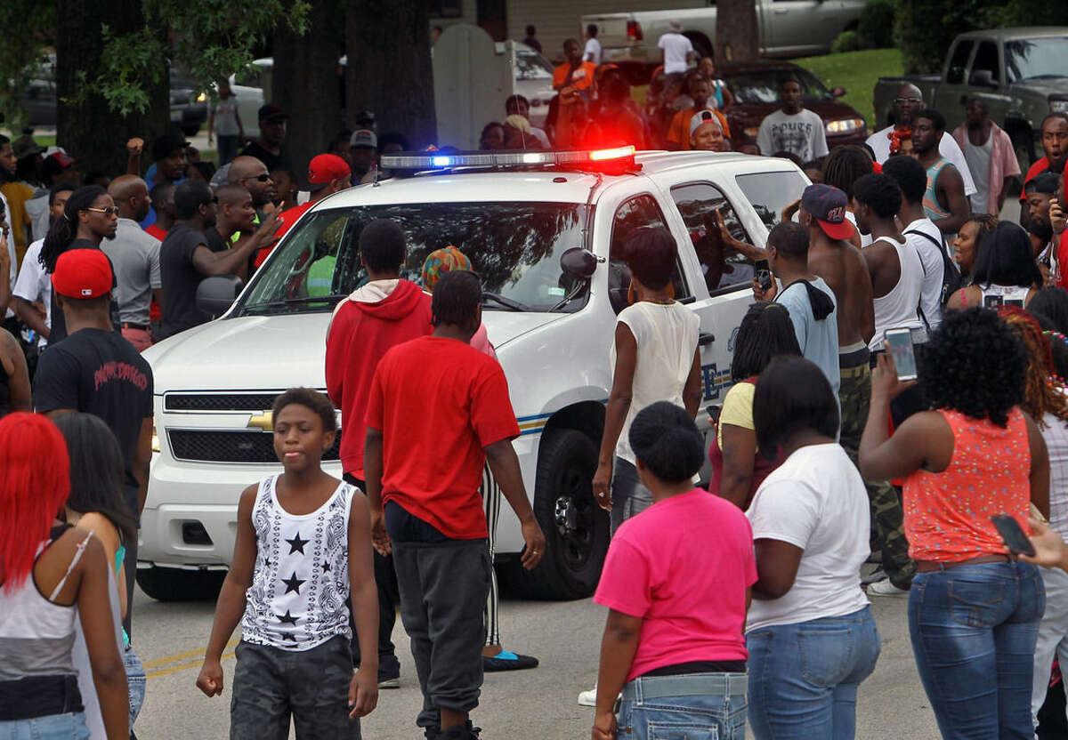 Protesters bang on the side of a police car Sunday evening, Aug. 10, 2014, in Ferguson, Mo. A few thousand people have crammed the street where a black man was shot multiple times by a suburban St. Louis police officer. The candlelight vigil Sunday night was for 18-year-old Michael Brown, who died a day earlier. Police say he was unarmed. (AP Photo/St. Louis Post-Dispatch, J.B. Forbes) EDWARDSVILLE INTELLIGENCER OUT; THE ALTON TELEGRAPH OUT