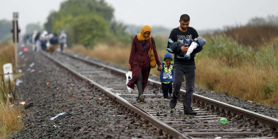 A family arrives at a migrant camp for asylum seekers on the railway track near Roszke, southern Hungary in Roszke, Thursday, Sept. 10, 2015. Leaders of the United Nations refugee agency warned Tuesday that Hungary faces a bigger wave of 42,000 asylum seekers in the next 10 days and will need international help to provide shelter on its border. (AP Photo/Matthias Schrader)