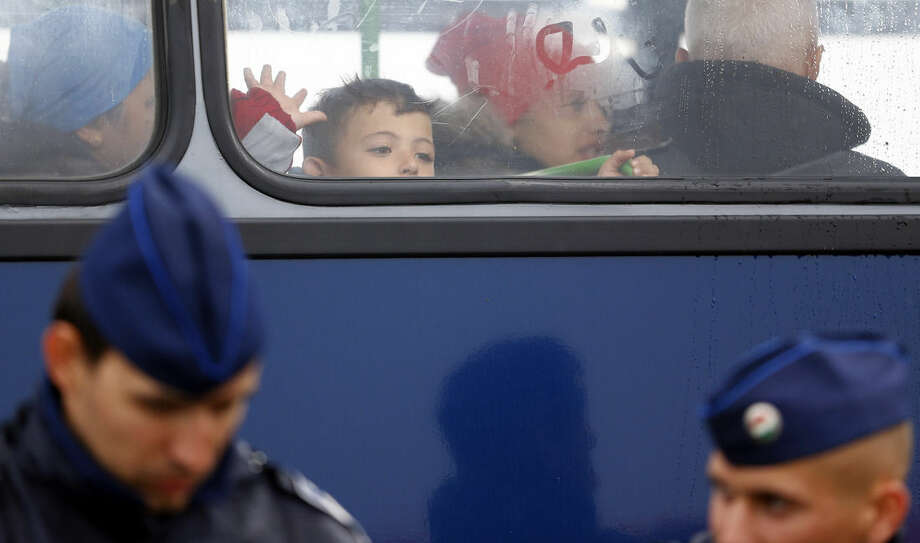A young boy looks waves out of a bus window as he leaves a migrant camp for asylum seekers near Roszke, southern Hungary in Roszke, Thursday, Sept. 10, 2015. Leaders of the United Nations refugee agency warned Tuesday that Hungary faces a bigger wave of 42,000 asylum seekers in the next 10 days and will need international help to provide shelter on its border, where newcomers already are complaining bitterly about being left to sleep in frigid fields. (AP Photo/Matthias Schrader)
