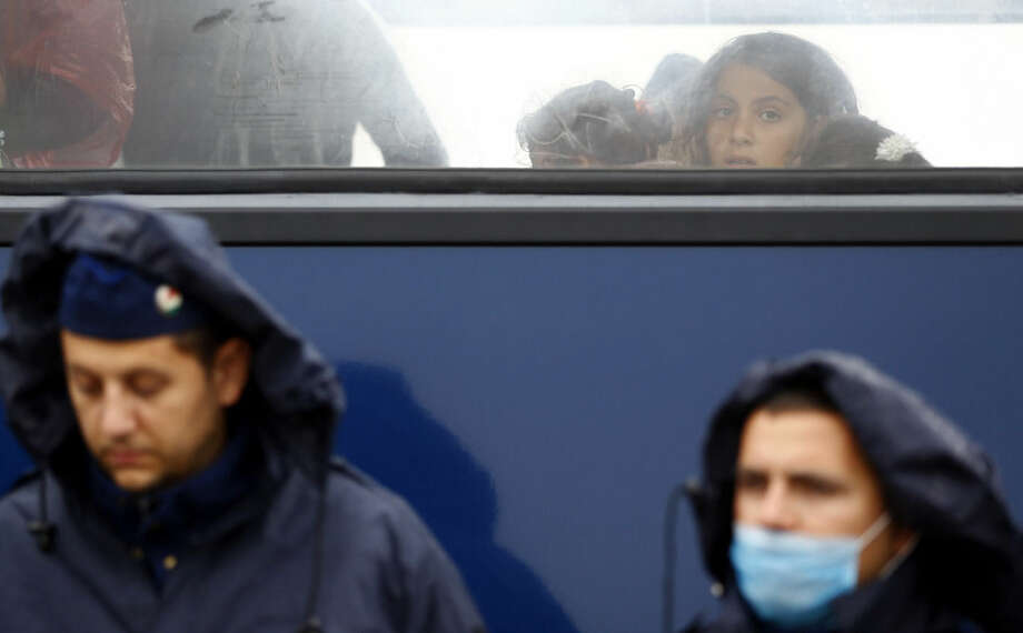 A young woman looks out of a bus window as she leaves a migrant camp for asylum seekers near Roszke, southern Hungary in Roszke, Thursday, Sept. 10, 2015. Leaders of the United Nations refugee agency warned Tuesday that Hungary faces a bigger wave of 42,000 asylum seekers in the next 10 days and will need international help to provide shelter on its border, where newcomers already are complaining bitterly about being left to sleep in frigid fields. (AP Photo/Matthias Schrader)