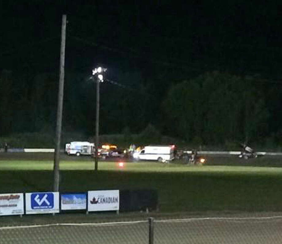 This image provided by Logan Messerly shows ambulances on the scene at Canandaigua Motorsports Park on Saturday Aug. 9, 2014 in Canandaigua, N.Y. Authorities are investigating a serious crash that injured one person at a New York dirt track where Tony Stewart was racing on the eve of a NASCAR race. (AP Photo/Logan Messerly)