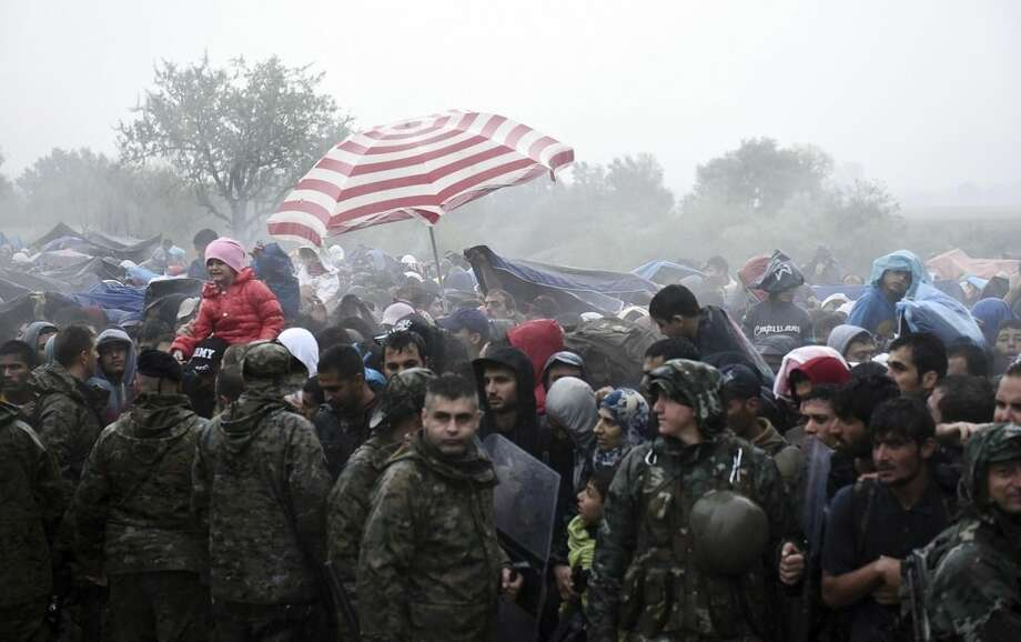 Refugees and migrants wait to pass from the northern Greek village of Idomeni to southern Macedonia, Thursday, Sept. 10, 2015. Thousands of people, including many families with young children, braved torrential downpours to cross Greece's northern border with Macedonia early Thursday, after Greek authorities managed to register about 17,000 people on the island of Lesbos in the space of a few days, allowing them to continue their journey north into Europe. (AP Photo/Giannis Papanikos)