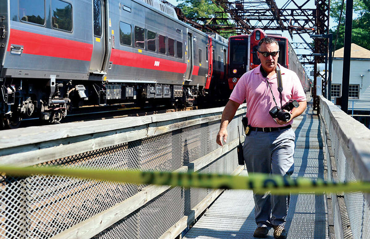 Hour photo / Erik Trautmann Westport police investigate the death of a man on the tracks north of the Saugatuck River bridge Wednesday.