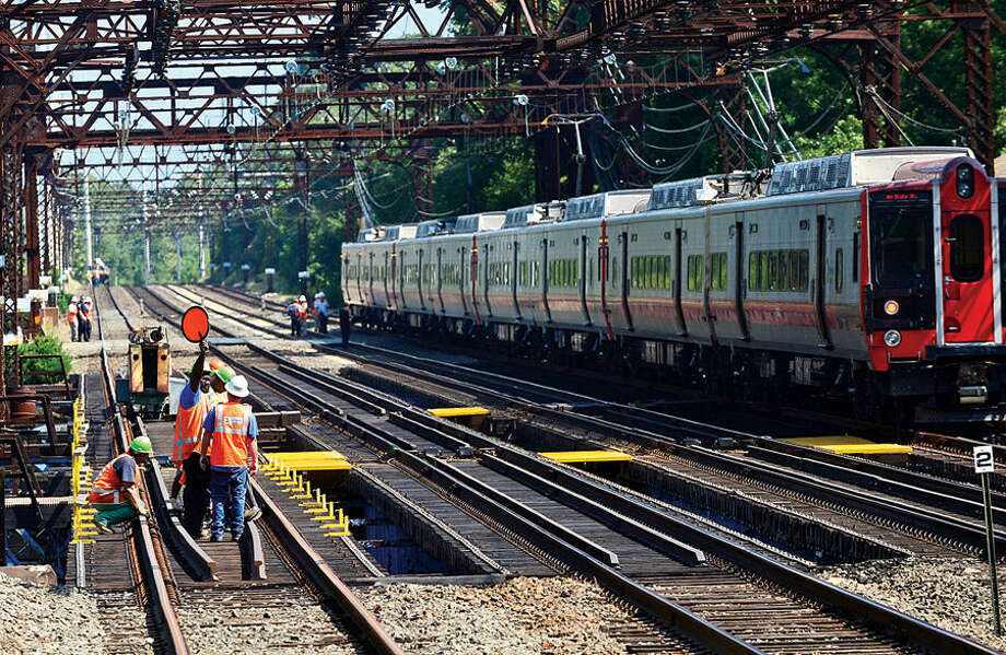 Hour photo / Erik Trautmann Metro-North personnel slow oncoming trains as Westport police investigate the death of a man on the tracks north of the Saugatuck River bridge Wednesday.