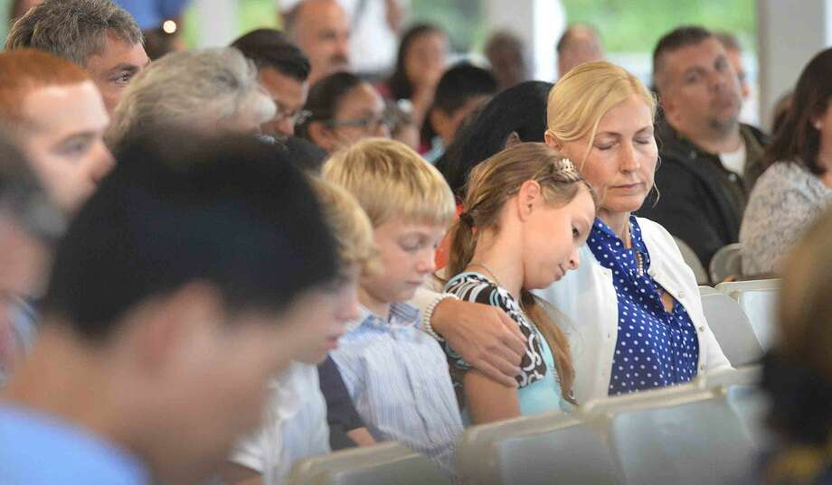 Hour Photo/Alex von KleydorffDuring the Connecticut Remembers September 11th Memorial Ceremony Tanja Vadas holds her daughter Kendra next to her while the family listens for their uncle Bradley's name to be called.