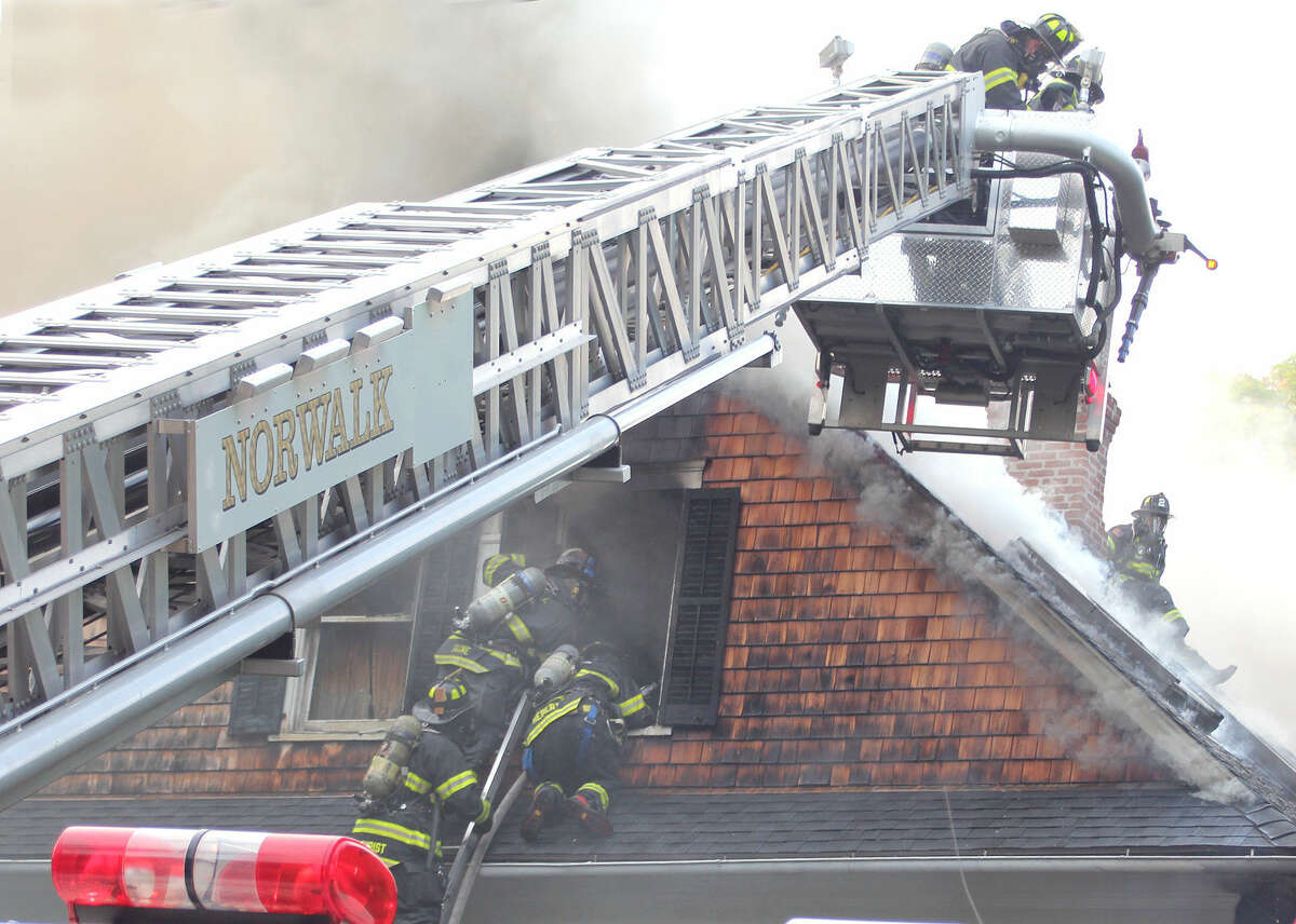 Hour photo / Chris Bosak Firefighters battle a fire at 1 Cannon St. in Norwalk on Monday evening.