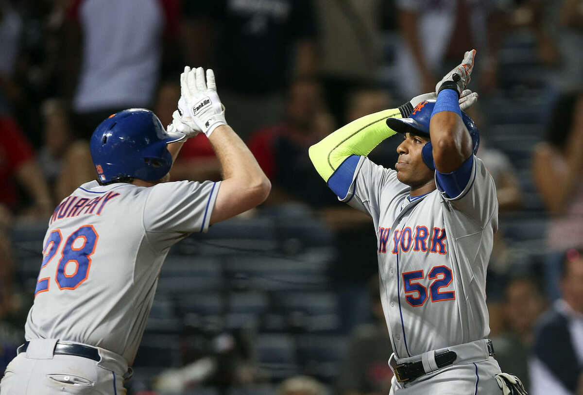 New York Mets' Yoenis Cespedes (52) celebrates with teammate Daniel Murphy after hitting two-run home run during the ninth inning of a baseball game against the Atlanta Braves on Friday, Sept. 11, 2015, in Atlanta. (AP Photo/John Bazemore)