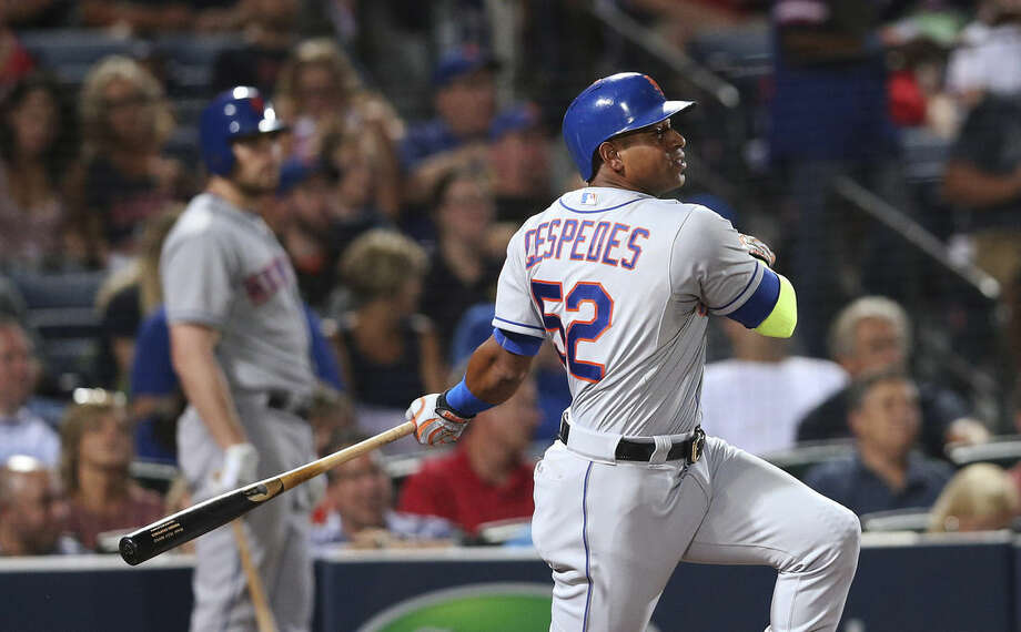 New York Mets' Yoenis Cespedes follows through on an RBI double during the third inning of a baseball game against the Atlanta Braves on Friday, Sept. 11, 2015, in Atlanta. (AP Photo/John Bazemore)