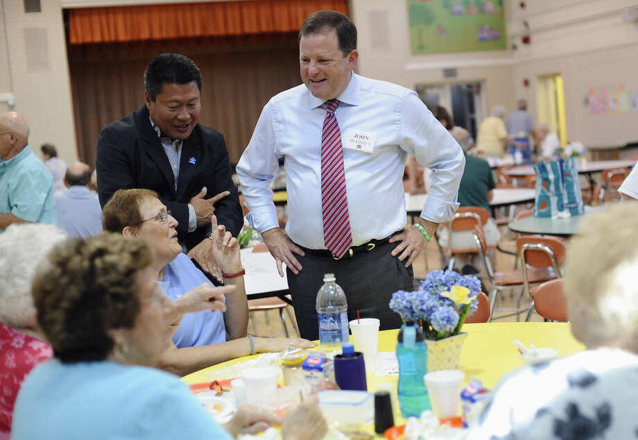 Republican candidate for Connecticut governor John McKinney, center, and State Rep. Tony Hwang, R-Fairfield, left, talk with seniors during a campaign stop at the town's senior center, Monday, Aug. 11, 2014, in Fairfield, Conn. McKinney will face Republican Tom Foley in Tuesday's primary. (AP Photo/Jessica Hill)