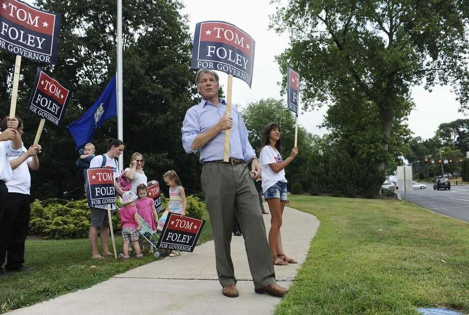 Republican candidate for Connecticut governor Tom Foley, center, greets commuters off an exit during rush hour, Monday, Aug. 11, 2014, in West Hartford, Conn. Foley will face Republican John McKinney in Tuesday's primary. (AP Photo/Jessica Hill)