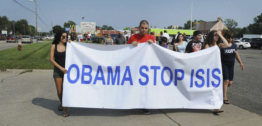 Protestors call on President Barack Obama to help end the bloodshed of Iraqi Christians as hundreds demonstrate against the terrorist group ISIS in Sterling Heights, Michigan on Sunday, Aug.10, 2014. (AP Photo/Detroit News, Brandy Baker)