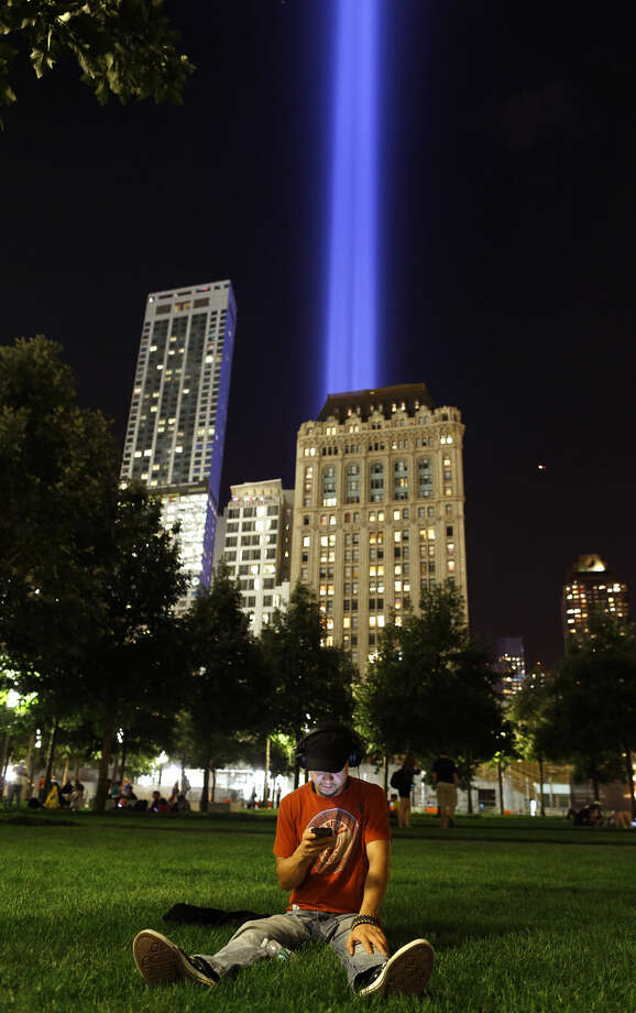 FILE- In this Sept. 11, 2014 file photo, a visitor to the World Trade Center complex in New York sits in the grass as a Tribute in Light rises from behind the surrounding buildings. An estimated 20,000 people flocked to the memorial plaza on the anniversary evening in 2014, the first year the public was able to visit on the day. (AP Photo/Julie Jacobson, File)