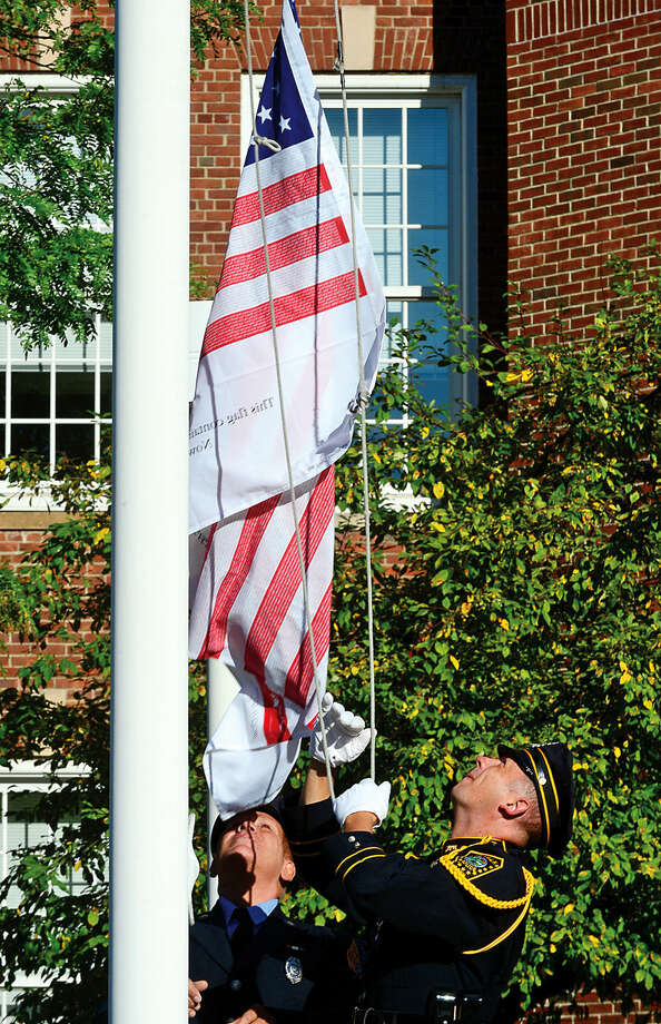 Hour photo / Erik Trautmann Honor guardsmen Norwalk Firefighter Mike Fratella and Norwalk Police Officer Gabe DeMott raise the flag to half mast as Norwalk holds the annual 9-11 Remembrance ceremony in the plaza at the front entrance of City Hall Friday.